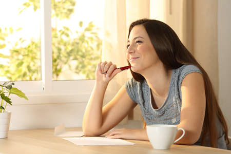 Happy girl thinking before handwriting a letter on a table at home Stock Photo