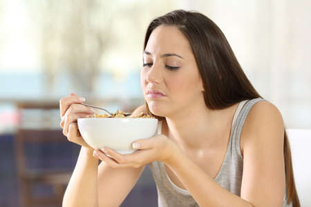 disgusted: Disgusted woman eating cereals with bad taste at home
