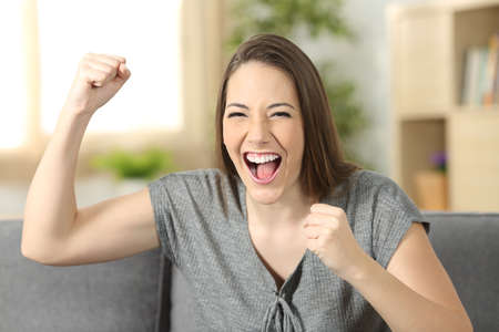 Excited woman looking at you sitting on a sofa in the living room at home