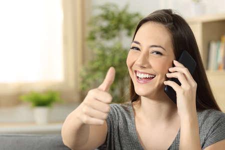Mujer que habla en una llamada de teléfono que le mira sentada en un sofá en la sala de estar en el país