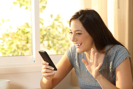 Happy girl waving during an on line phone video call at home