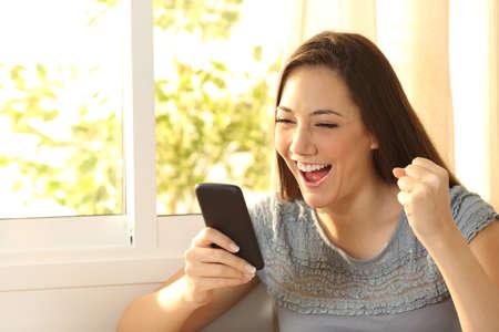 집에서 스마트 폰으로 콘텐츠를 시청하는 단일 흥분된 여성 스톡 콘텐츠