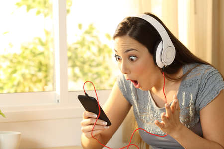 Amazed woman listening music finding offers on line in a smart phone in her room Stock Photo