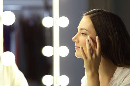 Side view portrait of a single woman checking for wrinkles looking at a make up mirror 스톡 콘텐츠