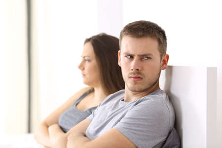 Angry couple after argument looking at another side sitting on the bed at home Stock Photo