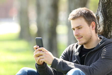 Portrait of a single boy reading messages in a smart phone sitting outdoors in a park Stock Photo