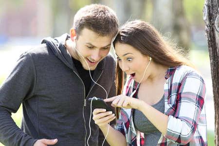 놀랄만 한 커플 서있는 음악을 듣고 공원에서 야외 스마트 폰에서 미디어 콘텐츠를보고 스톡 콘텐츠