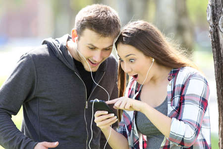 Amazed couple standing listening to music on line and watching media content in a smart phone outdoors in a park Imagens - 81952647
