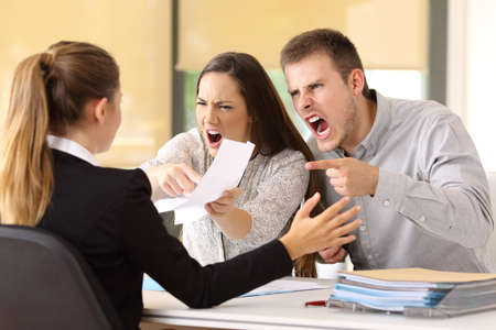 Angry couple claiming and shouting to an office worker