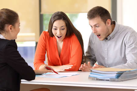 Two amazed customers reading contract conditions at office