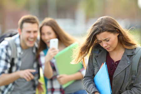 Bullying victim being video recorded on a smartphone by classmates in the street with a unfocused background Foto de archivo