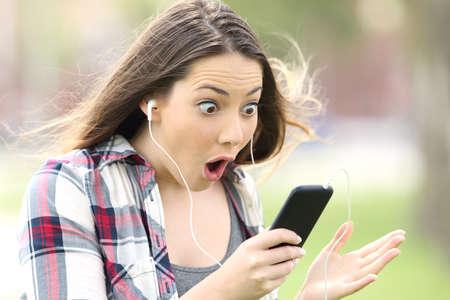 Ragazza sorpresa ascoltando la musica in linea e guardando contenuti multimediali all'aperto in un parco Archivio Fotografico - 81952763