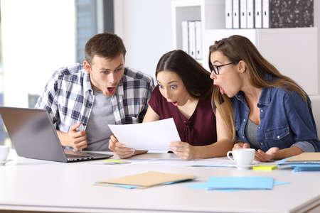 Drie verbaasde werknemers die een papieren document op kantoor lezen Stockfoto
