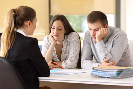 Bad saleswoman trying to convince to an unconvinced customers at office