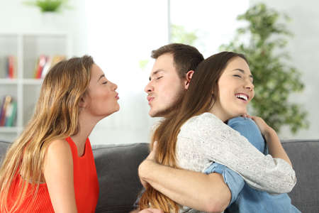 Boy cheating to his girlfriend with her best friend sitting on a couch at home Stock Photo - 81952937