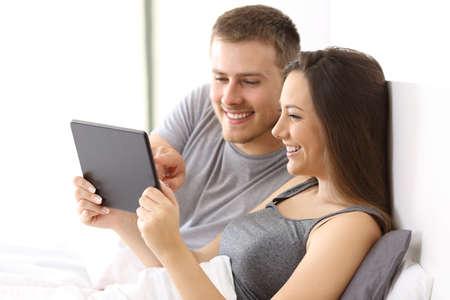 Pareja viendo los medios de comunicación juntos juntos en línea en una tableta en la cama de un apartamento Foto de archivo - 82083478