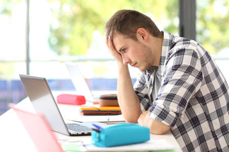 Side view of a single frustrated student trying to solve difficult problem on line sitting in a desk in classroom Stockfoto