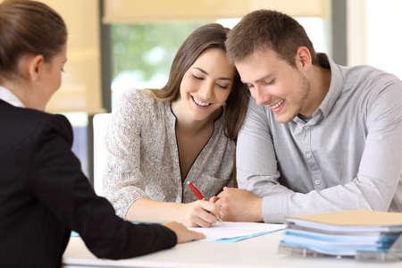 幸せなカップルが一緒に事務所で契約書に署名 写真素材