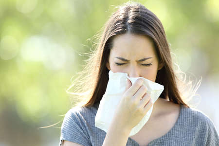 Front view of a single girl sneezing and blowing in a wipe outdoors with a green background