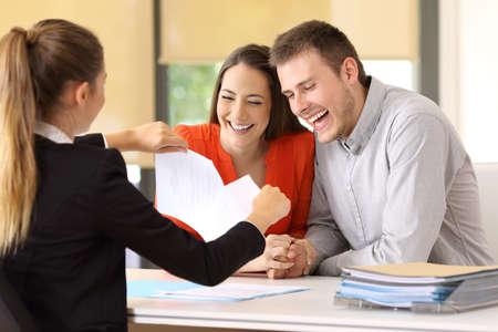 계약을 끝내고 사무실에서 그것을 해치는 행복한 고객의 커플 스톡 콘텐츠