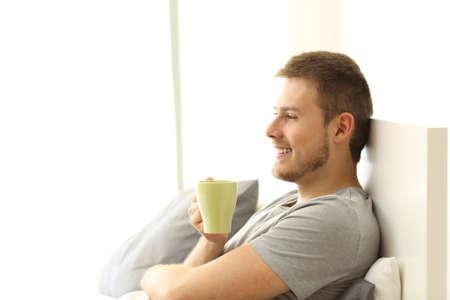 朝食をとると考えてアパートのベッドの上のコーヒー カップを保持している幸せな男の側面図