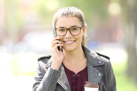 Front view of a fashion satisfied girl talking on the phone and looking at you in the street