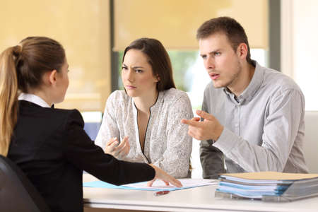Angry couple claiming to a businesswoman at office