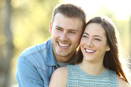 幸せなカップルが公園の側を見て完璧な笑顔でポーズ
