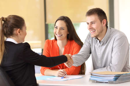 Couple of happy customers handshaking with worker after a deal at office Stock Photo - 82083521