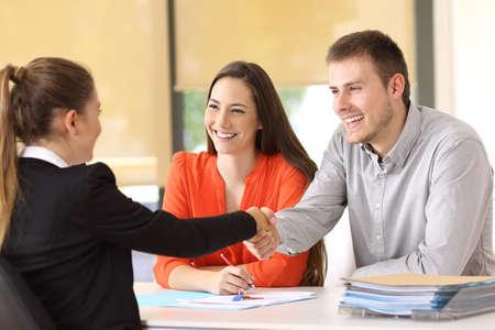 Par de clientes felices apretón de manos con el trabajador después de un acuerdo en la oficina Foto de archivo - 82083521