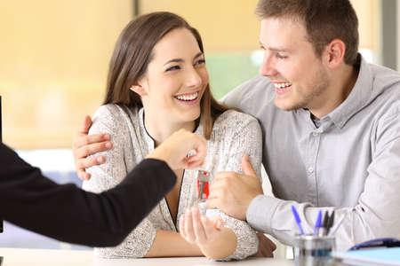 Glückliches Paar, welches die neuen Hausschlüssel im Immobilienbüro empfängt
