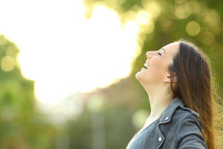 Zijaanzichtportret van een maniervrouw die verse lucht in openlucht met een groene achtergrond inademt