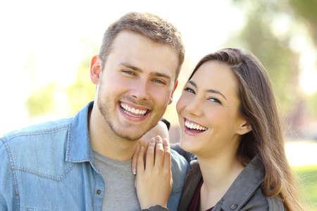 Vorderansicht eines Paares , das draußen mit perfektem Lächeln und weißen Zähnen aufwirft und auf einem Park mit einem grünen Hintergrund betrachtet Standard-Bild