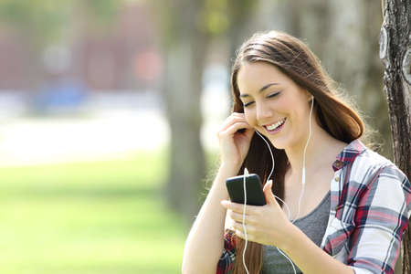 Happy girl listening on line music and watching media content in a smart phone in a park