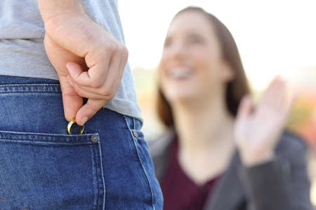 Cheater hiding wedding ring in a pocket in foreground while is dating with his lover outdoors