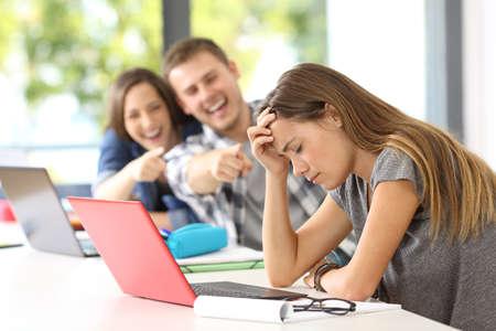 Los compañeros de clase intimidan a una víctima triste en un aula Foto de archivo - 83043313