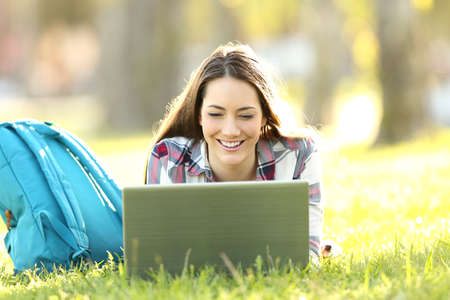 Front view of a happy student watching on line content in a laptop lying on the grass of a park Stock Photo