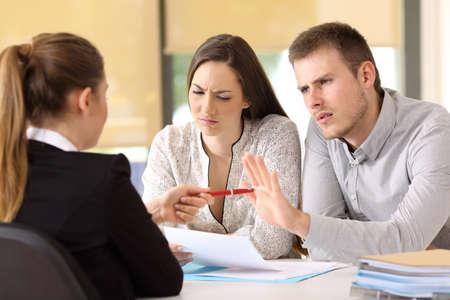 Verkoopster die een pen aanbiedt aan een paar boze klanten die weigert een contract op kantoor te zingen