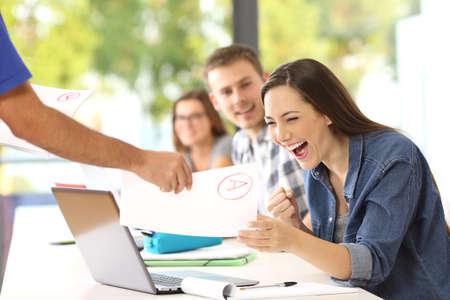 Opgewonden student die een goedgekeurd examen ontvangt van de leraar in een klaslokaal Stockfoto