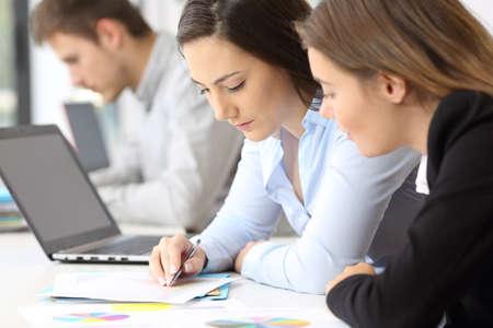 コワーキング オフィスに紙の書類のデータを分析集中の 2 つの従業員のクローズ アップ