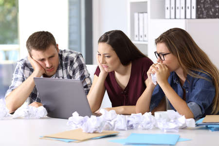 Three frustrated entrepreneurs trying to do a difficult job on line at office