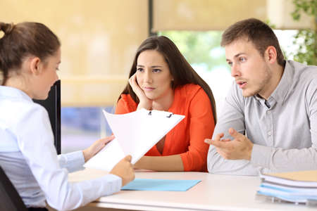 concern: Sad couple with problems talking in a marriage counseling Stock Photo