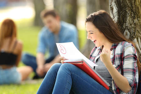 Excited student checking an approved exam sitting on the grass in a park with unfocused people in the background