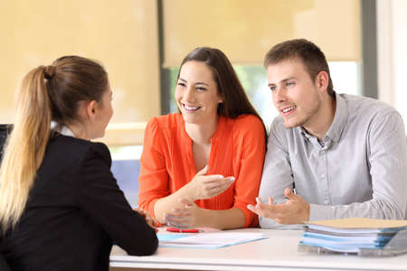 Two happy customers having a conversation with an office worker