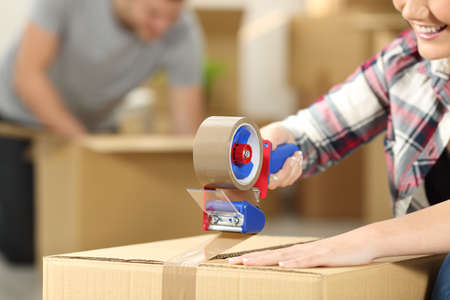 Close up of a happy couple moving home packing boxes and sealing with tape sitting on the floor