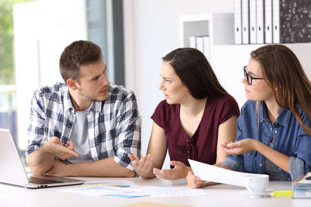Three employees having a job conversation sitting in a desktop at office