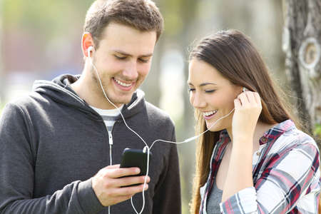 Happy couple of teenagers sharing on line music and watching media content in a smart phone outdoors in a park
