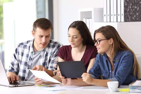 Three employees coworking on line with multiple devices at office