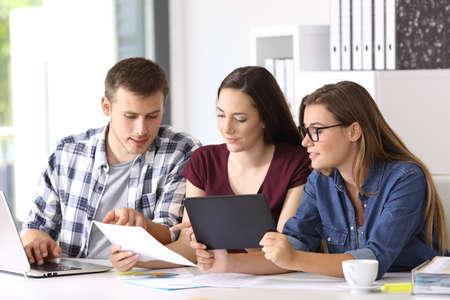 Tres empleados coworking en línea con múltiples dispositivos en la oficina