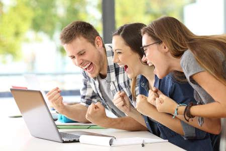 Zijaanzicht van drie opgewonden studenten die goed nieuws samen online in een laptop zitting in een bureau in een klaslokaal lezen